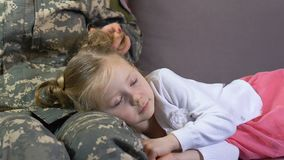 Femme soldat frottant la fille de sommeil détendant sur le sofa, connexion de famille banque de vidéos