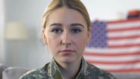 Femme soldat triste regardant la caméra avec le drapeau américain sur le fond, Jour du Souvenir banque de vidéos