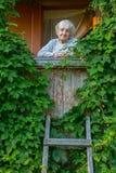 Femme solitaire pluse âgé sur le porche, couvert de verdure de la maison rurale photos stock