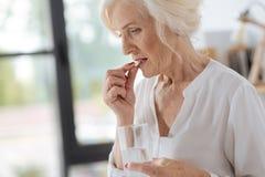 Femme sombre triste mettant une pilule à sa bouche image libre de droits