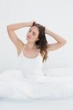 Femme somnolente étirant ses bras dans le lit Photo libre de droits