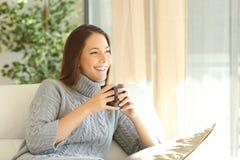 Femme songeuse à la maison en hiver photographie stock libre de droits