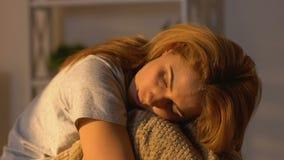 Femme songeuse étreignant des genoux, pièce de remplissage de soleil de matin, rêve romantique banque de vidéos