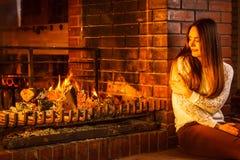 Femme songeuse détendant à la cheminée Maison d'hiver Photo stock