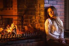Femme songeuse détendant à la cheminée Maison d'hiver Images libres de droits