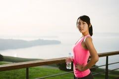 Femme songeuse de forme physique regardant l'océan Image stock