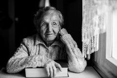 Femme songeuse pluse âgé avec un livre près de la fenêtre Photo stock