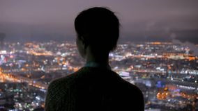 Femme songeuse regardant la ville de nuit du gratte-ciel clips vidéos