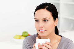 Femme songeuse retenant une cuvette de café Photo stock