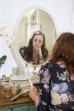 Femme songeuse s'asseyant à la coiffeuse Image stock