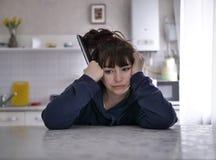 Femme songeuse s'asseyant avec ? t?l?commande sur un fond brouill? de la cuisine photo libre de droits