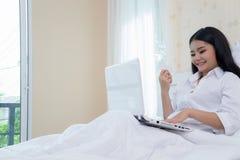 Femme songeuse se trouvant sur le lit et faisant des emplettes en ligne avec le carnet photos libres de droits