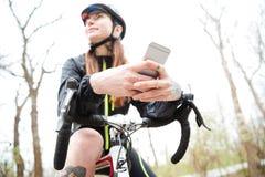 Femme songeuse sur le vélo utilisant le téléphone portable en parc Image libre de droits