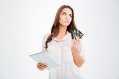 Femme songeuse tenant la carte de crédit et à l'aide de la tablette Photo libre de droits