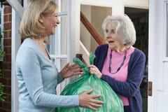Femme sortant des déchets pour le voisin plus âgé images libres de droits