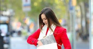 Femme sortant un téléphone d'un sac à main clips vidéos