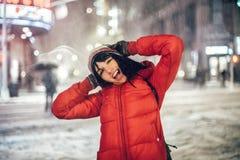Femme sortie heureuse ayant l'amusement sur la rue de ville de New York sous la neige au chapeau et à la veste de port d'horaire  photos stock