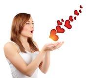 Femme soufflant les coeurs rouges Images stock