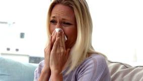 Femme soufflant son nez sur le sofa banque de vidéos