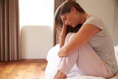 Femme souffrant de la dépression se reposant sur le lit dans des pyjamas image libre de droits