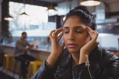 Femme souffrant du mal de tête avec l'ami à l'arrière-plan Image stock