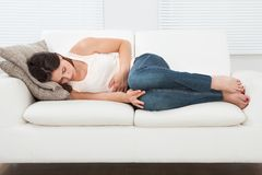 Femme souffrant du mal de ventre sur le sofa Photo libre de droits