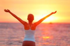 Femme soulevant des bras à la plage pendant le coucher du soleil Image stock