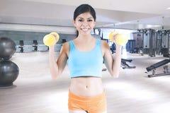 Femme soulevant deux haltères au centre de fitness Photographie stock libre de droits