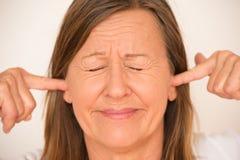Femme soumise à une contrainte bloquant des oreilles avec le doigt Images stock