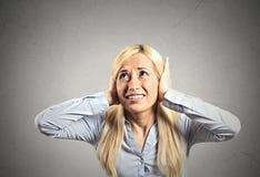 Femme soumise à une contrainte couvrant ses oreilles Image libre de droits