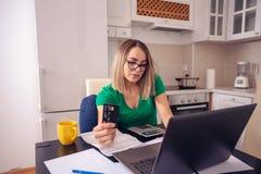 Femme soumise à une contrainte d'affaires à la maison travaillant - budget de planification et fi images stock