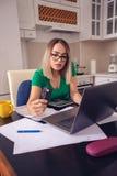 Femme soumise à une contrainte d'affaires à la maison travaillant - factures de paiement photos stock