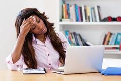 Femme soumise à une contrainte d'afro-américain à l'ordinateur images stock