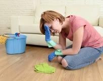 Femme soumise à une contrainte et fatiguée nettoyant la maison lavant le plancher sur ses genoux Photographie stock libre de droits