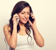 Femme soumise à une contrainte fâchée malheureuse tenant deux téléphones portables près du Image stock