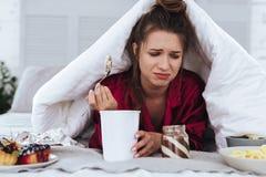 Femme soumise à une contrainte mangeant la grande crème glacée et pleurer  photo stock
