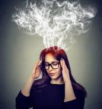 Femme soumise à une contrainte pensant la vapeur trop dure sortant de la tête Photographie stock libre de droits