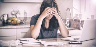 Femme soumise à une contrainte regardant vers le bas des factures Photographie stock libre de droits