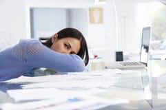 Femme soumise à une contrainte travaillant à l'ordinateur portable dans le siège social photo stock
