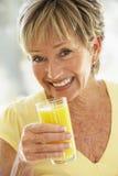 Femme souriant à l'appareil-photo buvant du jus d'orange Images libres de droits