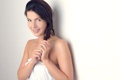 Femme souriant à l'appareil-photo tout en tenant ses cheveux photographie stock