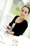 Femme souriant à l'appareil-photo utilisant le comprimé Photographie stock libre de droits