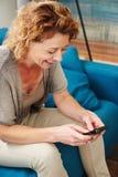 Femme souriant à la maison écrivant le texte au téléphone intelligent Photos libres de droits