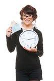 Femme souriant avec l'horloge et l'argent Photographie stock libre de droits