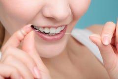 Femme souriant avec le fil dentaire photographie stock libre de droits