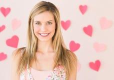 Femme souriant avec les papiers en forme de coeur coincés contre Backgr rose Photographie stock libre de droits