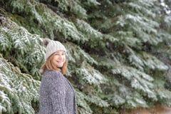 Femme souriant dans la neige à la ferme d'arbre de Noël images stock