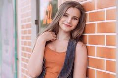 Femme souriant dehors veste de cuivre orange de blues-jean de chemise photos stock