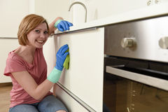 Femme souriant lavage et nettoyage heureux et positifs avec le tissu une cuisine moderne Photo libre de droits