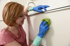 Femme souriant lavage et nettoyage heureux et positifs avec le tissu une cuisine moderne Image libre de droits